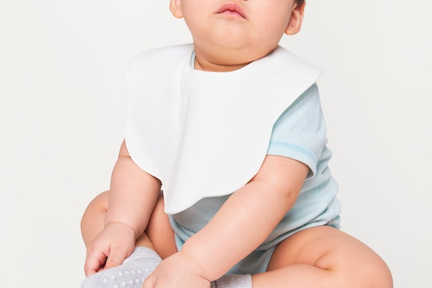 Baby wearing white apron in studio