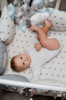 Baby in white clothes is lying in a child's bed