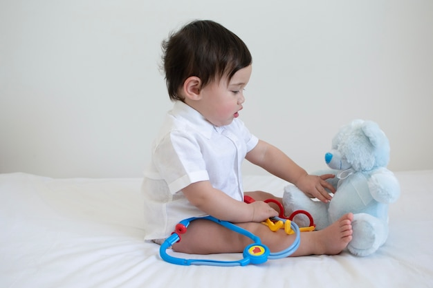 Baby in white shirt playing with medical equipment and check up if teddy bear is sick