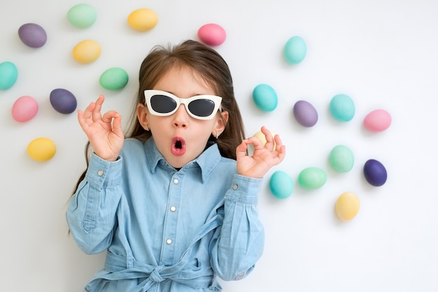 Baby on a white wall with easter eggs