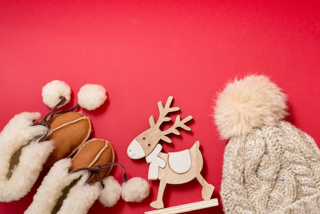 Baby winter clothes booties and hat on red background with wood toy deer, copy space