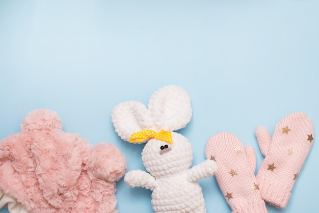 Baby winter clothes pink hat and mittens on blue background with white toy rabbit, copy space