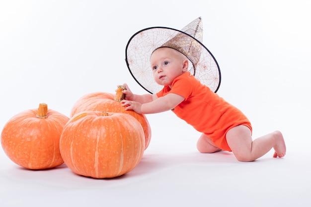 Шляпа ведьмы младенца на белом сидя перед тыквой