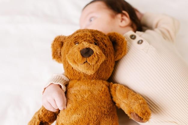 Ребенок с игрушкой-медведем на кровати, вид сбоку