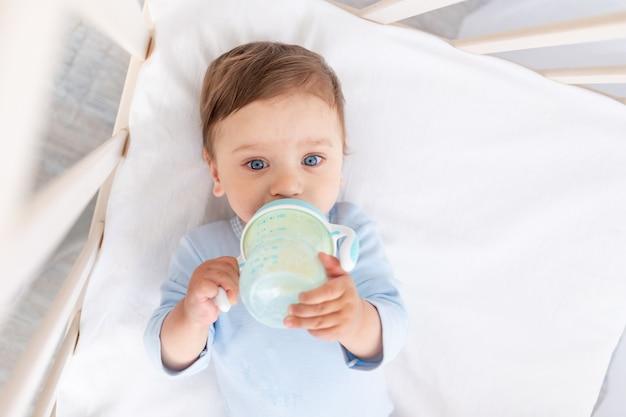 아기 침대 식사에 그의 손에 우유 병, 베이비 푸드 개념