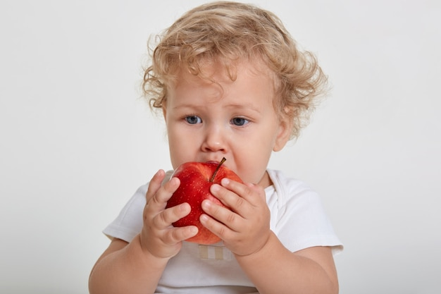 Baby with apple posing isolated over white