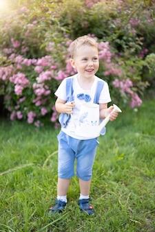 화창한 여름날 파란 눈을 가진 아기는 꽃에 물을 주는 깡통을 들고 웃는다