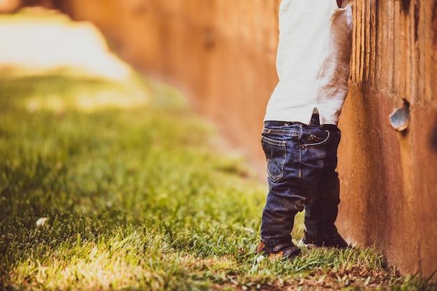 Ребенок в синих джинсах пытается ходить