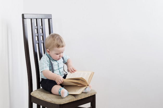 Ребенок с книгой, сидя на стуле на белом