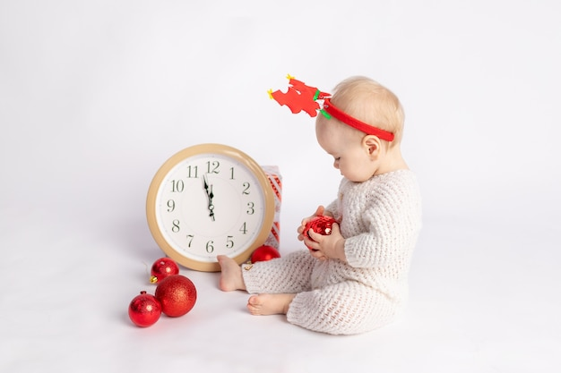 Baby with clock, gift and christmas balls on white isolated background, space for text, new year and christmas concept
