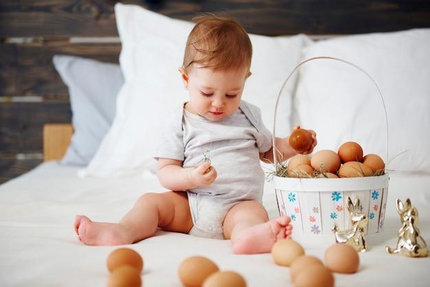 Bambino con cesto di uova pasquali