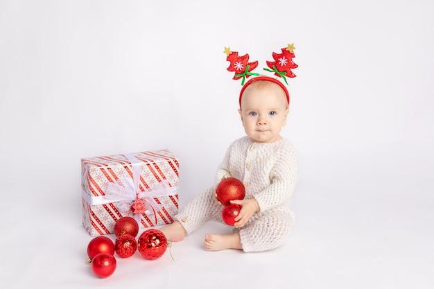흰색 격리된 배경에 선물과 크리스마스 공을 든 아기, 텍스트, 새해 및 크리스마스 컨셉을 위한 공간