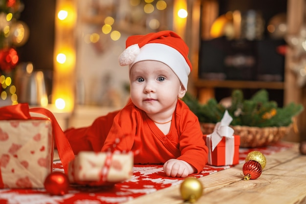 Baby with gift boxes on the table with christmas decorations