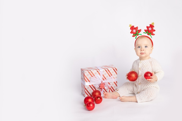 Baby with gift and christmas balls on white isolated background, space for text, new year and christmas concept
