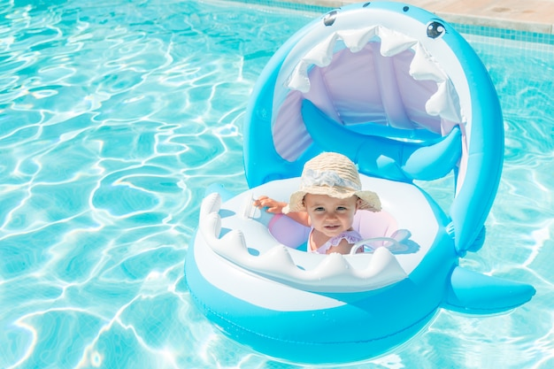 Baby with hat on a shark-shaped float in the pool