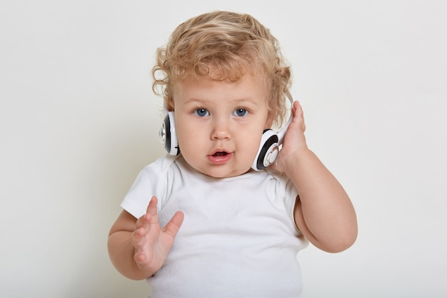 Baby with headphones looking directly at camera, keeping hand on ear phone, having curious facial expression