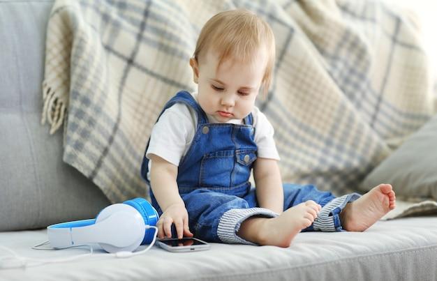 Ребенок с наушниками, сидя на диване