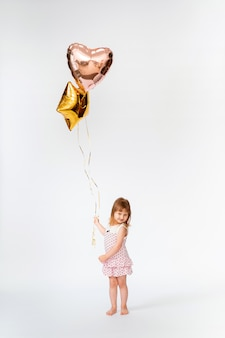 Baby with heart shaped balloons and stars on white