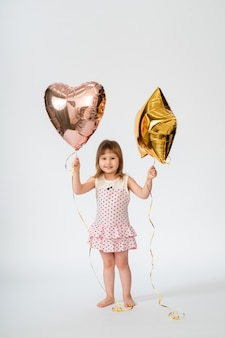 Baby with heart shaped balloons and stars