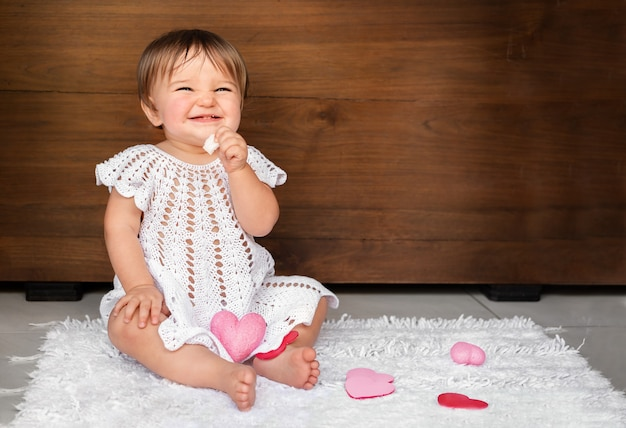 Baby with hearts on a wooden background. child gnaws white cookies