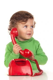 Baby with one years old playing with a red phone