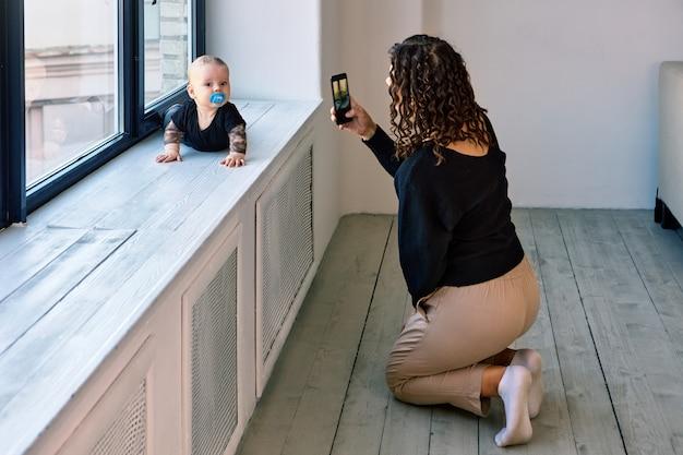 おしゃぶりを持った赤ちゃんが窓辺を這い、女性が写真を撮る