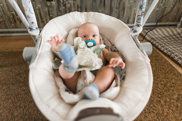 Baby with pacifier lying on baby carriage at home