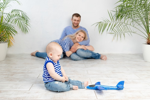 A baby with a plane in focus against the background of happy parents in a nautical image in vests having fun, the concept of travel and recreation