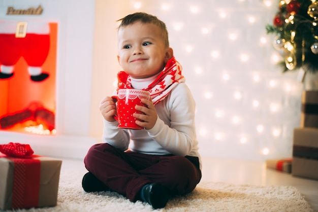 새해 전날과 크리스마스를 매력적인 크리스마스 트리 배경에 빨간 머그를 든 아기