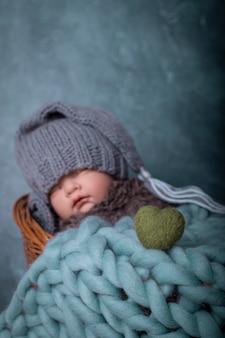침대 파란색 배경에서 잠자는 스타킹 모자를 쓴 아기 아기 사랑 녹색 심장