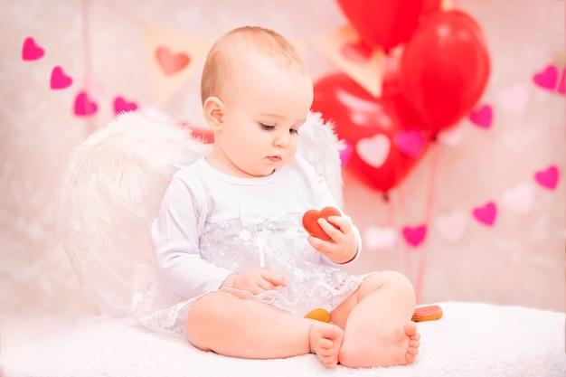 흰색 깃털 날개를 가진 아기는 발렌타인 데이의 상징 인 하트 모양의 쿠키를 먹는다.