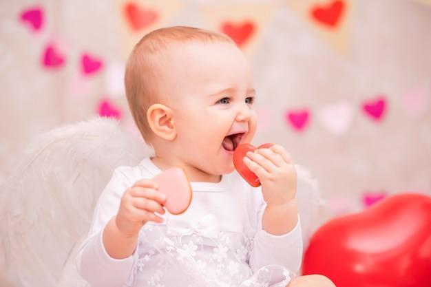 하얀 깃털 날개를 가진 아기가 하트 모양의 쿠키를 먹는다.