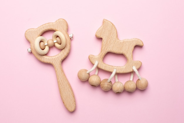 Baby wooden rattles and toys on pink