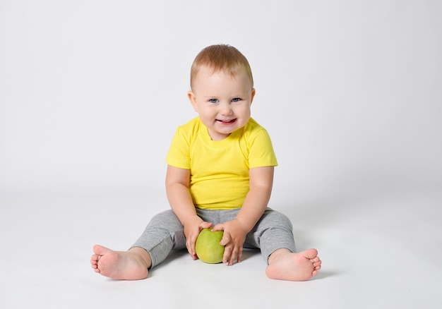 A baby in a yellow tshirt holds a green apple in his hands the child is sitting on a white background with a green apple