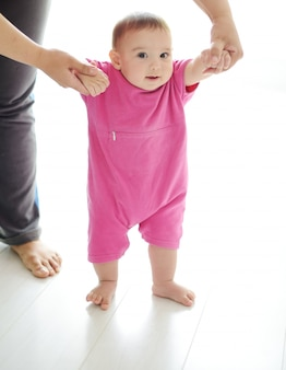 Baby принимая первые шаги с помощью мамы на белом фоне