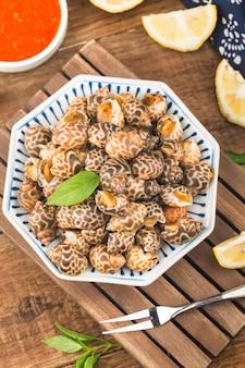 Морепродукты моллюсков babylonia areolata на миске, готовые к употреблению или приготовленные