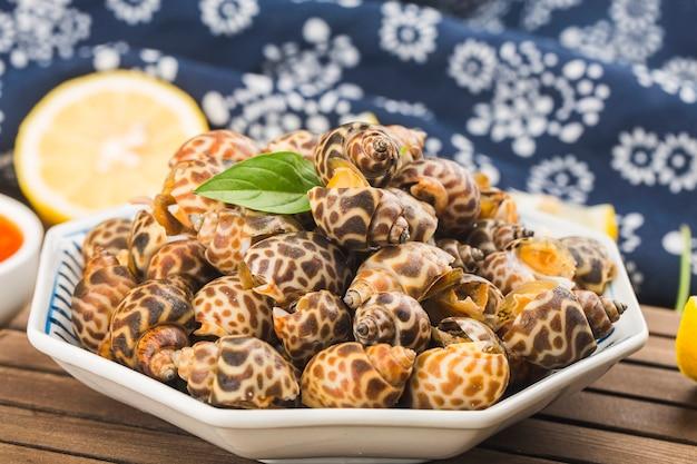 먹거나 요리할 준비가 된 그릇에 있는 바빌로니아 아레올라타 조개 해산물