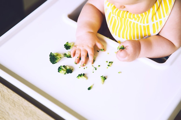 Babys first solid food baby eats and tastes with fingers vegetables broccoli in high chair
