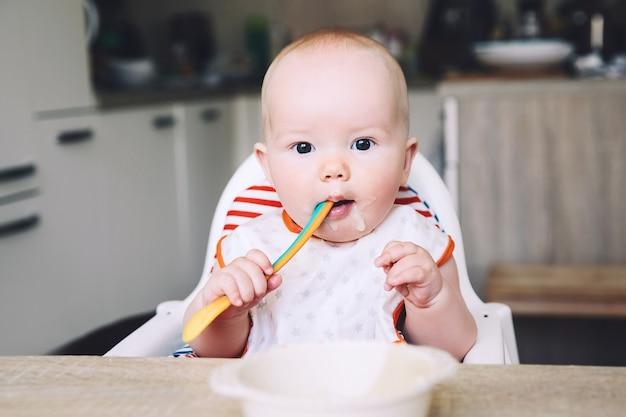 Первая твердая пища для малышей мать кормит маленького ребенка ложкой пюре повседневная жизнь пальцевое питание