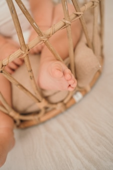 Babys legs closeup a small childs leg in a basket vertical photo of a small child space for text and...