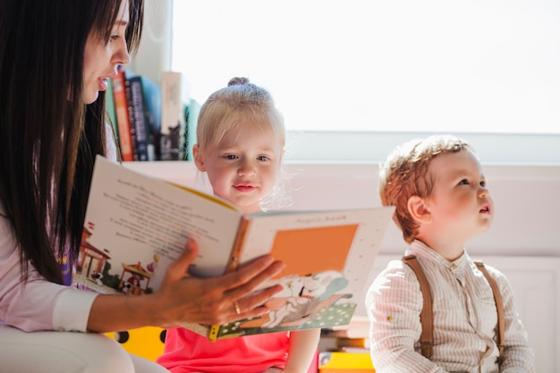 Babysitter showing book to girl