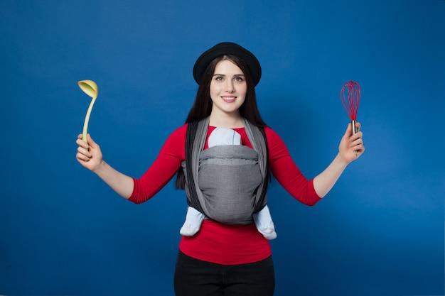 ひしゃくと泡立て器を手にした織りラップキャリアで赤ちゃんと一緒に赤ちゃんを着ている魅力的な若い母親。フリーハンドとアクティブな母性の概念のアイデア