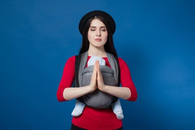 ひしゃくと泡立て器を手にした織りラップキャリアで赤ちゃんと一緒に赤ちゃんを着ている魅力的な若い母親。フリーハンドと平和な心の母性の概念のアイデア