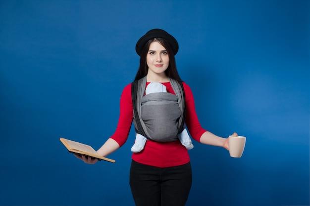 彼女の手にマグカップと本を備えた織りラップキャリアで赤ちゃんと赤ちゃんを身に着けている魅力的な若い母親。フリーハンドとアクティブな母性の概念のアイデア