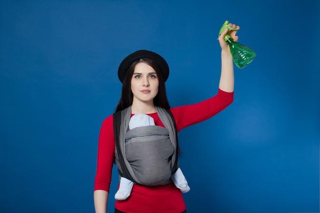 彼女の手にスプレーで織られたラップキャリアで赤ちゃんと赤ちゃんを身に着けている魅力的な若い母親。フリーハンドと家の掃除の母性の概念のアイデア