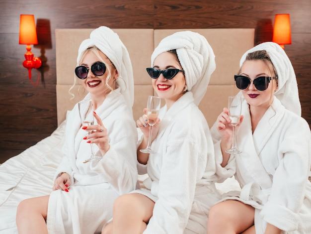 独身パーティーの楽しみ。サングラス、バスローブ、タオルターバンとシャンパンを身に着けた陽気な若い女性。裸の膝。