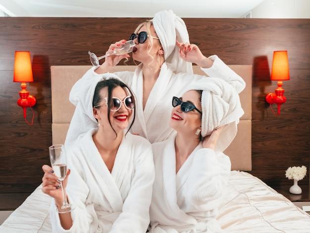 独身パーティーの楽しみ。サングラス、バスローブ、ターバンでシャンパンを飲む陽気な若い女性。余暇の喜び。