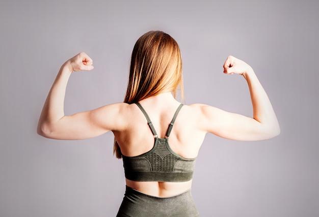 灰色の背景に分離された若いスポーティな筋肉女性の背中と手