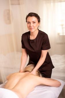웃고있는 물리 치료사의 허리와 어깨 마사지