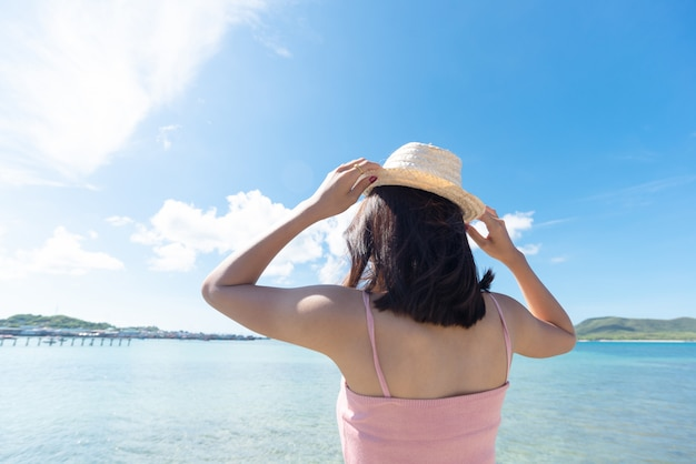 Back of asian woman tan skin wearing pink tank top and hold straw hat. she looking into the sea. summer travel. relaxing.